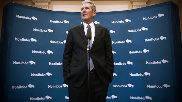 Brian Pallister parle, debout, derrière un micro et a les mains dans ses poches. On voit en arrière-plan plusieurs image du logo de la province (le mot Manitoba suivi d'une image stylisée de bison).