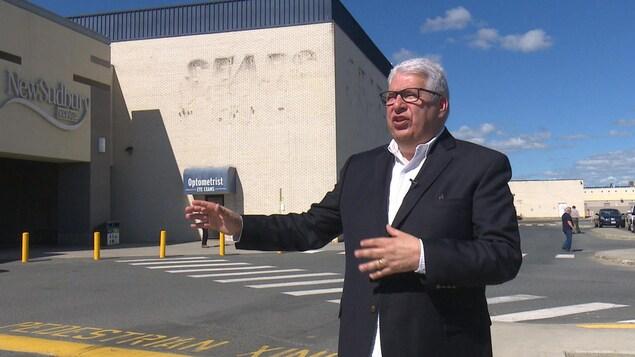 Brian Vendramin gesticule dans un terrain de stationnement devant un ancien magasin de Sears.