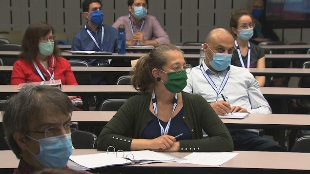 Des gens portant des masques écoutent dans une salle de classe.