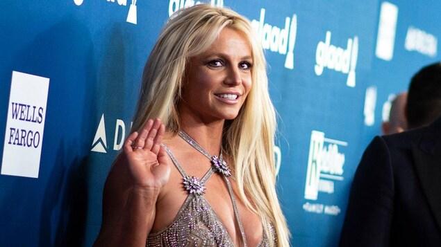 La chanteuse Britney Spears salue la caméra de la main lors d'un événement médiatique.