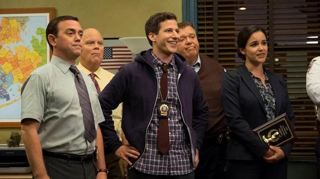 Cinq employés du poste de police se tiennent debout dans une pièce.