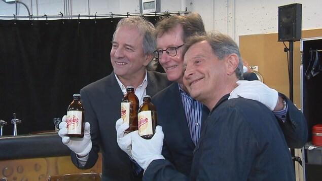 Les comédiens Michel Côté, Marc Messier et Marcel Gauthier qui tiennent une bouteille étiquetée Broue