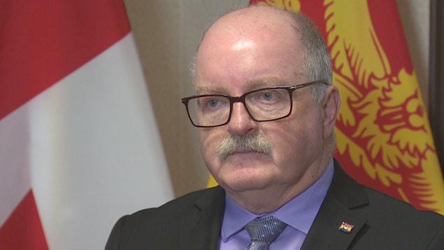 Bruce Fitch en mêlée de presse devant des drapeaux du Nouveau-Brunswick et du Canada.