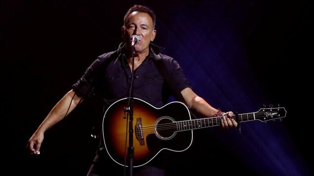 Un homme chante au micro accompagné d'une guitare.