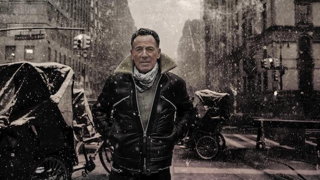 Bruce Springsteen, avec un manteau de cuir, pose dans une rue.
