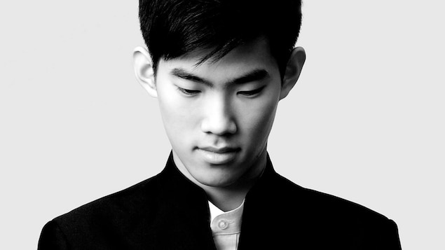 Un jeune homme regarde vers le sol, dans une photo en noir et blanc.
