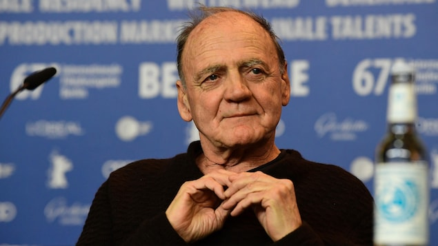 Un homme portant un chandail noir se tient les mains derrière une table sur laquelle sont déposés une bouteille et un micro lors d'une conférence de presse.