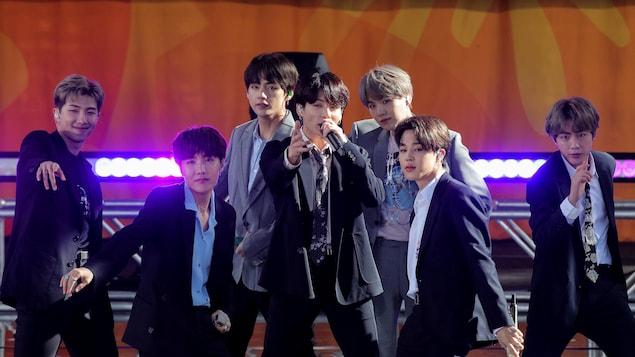 Sept jeunes hommes vêtus de complets sont sur scène lors d'une prestation.