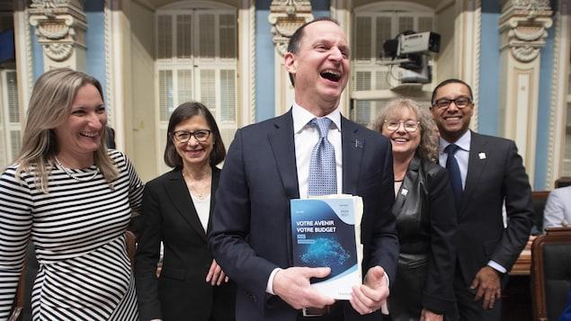 Eric Girard est tout sourire entouré d'autres élus de la CAQ.