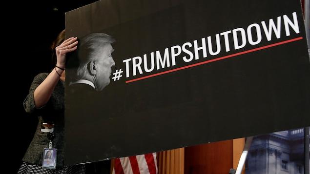 On peut lire sur la pancarte noire le mot-clic #TrumpShutDown