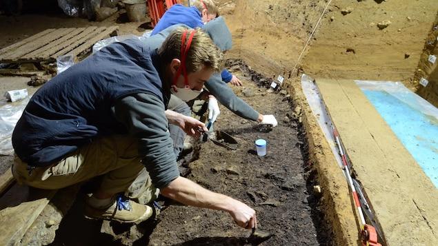 Des hommes travaillent dans la terre dans la grotte de Bacho Kiro.