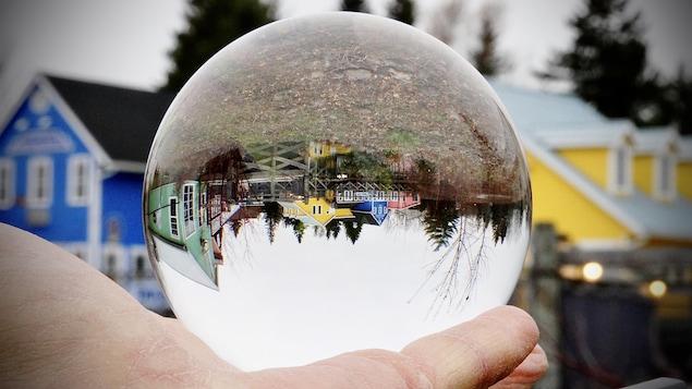 Des maisons qui apparaissent à l'envers à travers un globe.