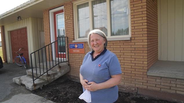 Une femme devant un bureau de poste.
