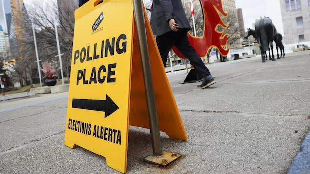 Un panneau indique un bureau de vote au centre-ville de Calgary pendant que des passants marchent sur un trottoir près d'un logo des Flames, l'équipe de hockey.