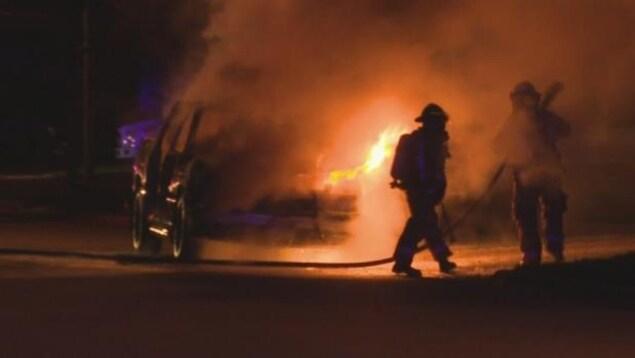 Des pompiers s'efforcent d'éteindre les flammes qui émergent de la camionnette utilisée par les suspects.