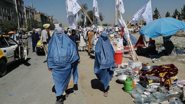 Deux femmes afghanes marchent près d'étals dans un marché, chacune vêtue d'une burqa bleue.