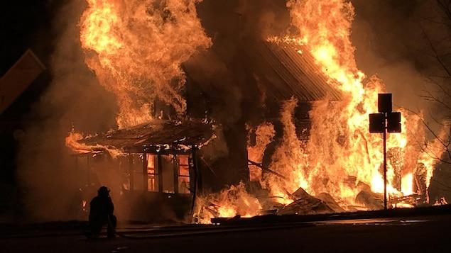 Un pompier combat un incendie. Une maison est complètement embrasée par d'imposantes flammes.