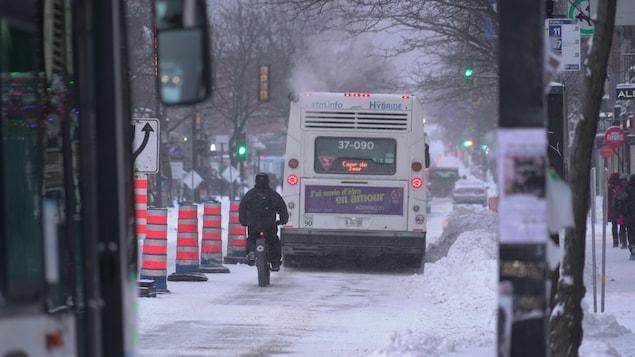 Un cycliste suit de près un autobus sur une chaussée enneigée.