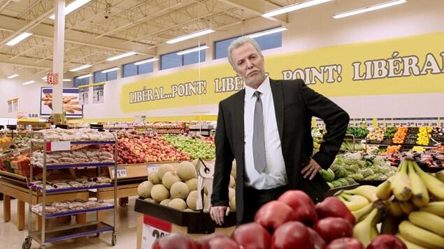 Un homme se tient debout en costume dans le rayon fruits et légumes d'une épicerie.