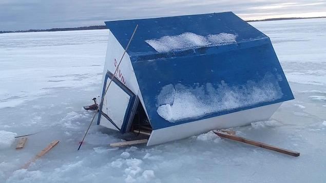 Une cabane a demi submergée dans la glace.