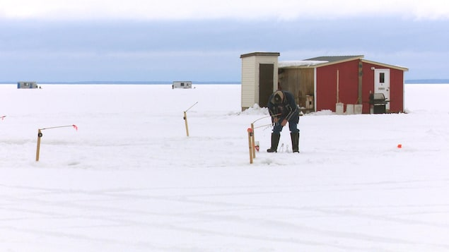 Un pêcheur se trouve à l'extérieur de sa cabane.