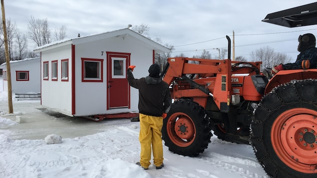 Tracteur qui dépose une cabane sur la glace à Sainte-Anne-de-la-Pérade
