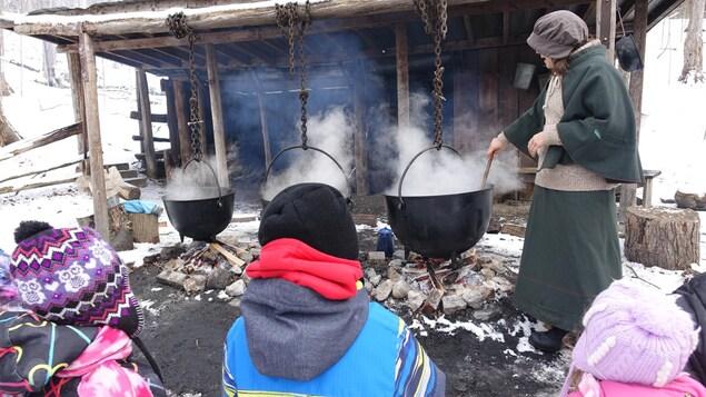 Des interprètes du Centre de conservation Kortright informent les visiteurs des techniques utilisées auparavant pour faire du sirop d'érable.