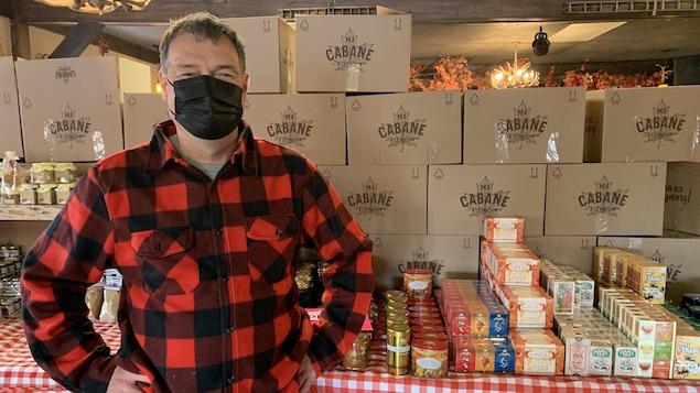 Richard Lessard se tient devant une table pleine de produits de l'érable.