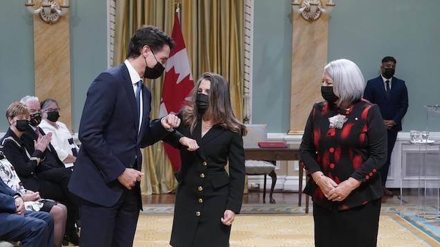 Chrystia Freeland et Justin Trudeau se saluent en se touchant de l'avant-bras.