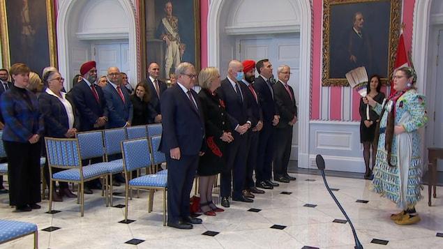 Les membres du cabinet Trudeau attendent en ligne pendant une prestation de danse autochtone.