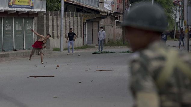 Des manifestants musulmans du Cachemire lancent des pierres sur des soldats indiens pendant le couvre-feu à Srinagar, en Inde, le vendredi 16 août 2019.