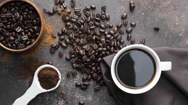 Du café torréfié, une tasse à café blanche avec du café noir, une serviette de couleur marron foncé avec une cuillère blanche remplie de café.