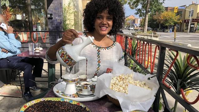 Une femme assise à la terrasse devant un homme qui parle au téléphone. Jebena à la main, elle verse le café dans des petites tasses rangées sur un plateau à coté de grains de café et de maïs soufflé.