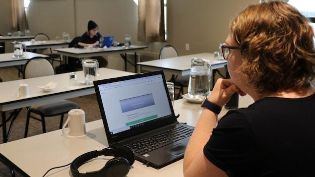 Deux personnes travaillent à leur ordinateur sur des tables individuelles.