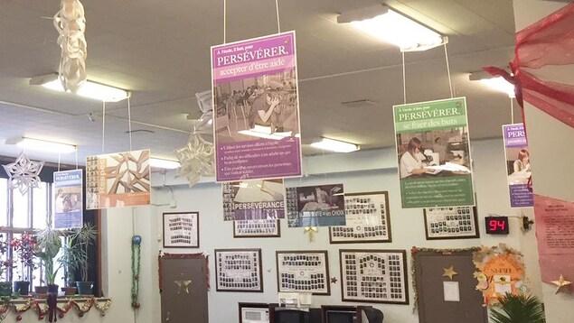 Des affiches suspendue au plafond de la cafétéria. Sur le mur du fond, des photos de diplômés.