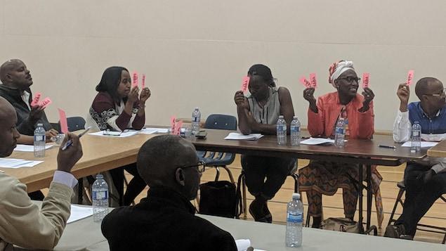Des membres de la CAFS tiennent des petits papiers dans leurs mains pendant qu'ils sont assis autour d'une table.