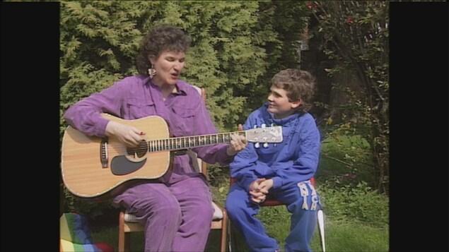 une dame assise dans un jardin qui chante et joue de la guitare et un garçon assis à côté d'elle.
