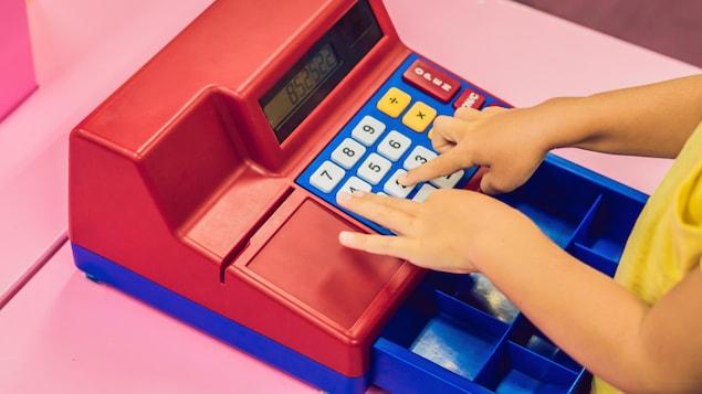 Les mains d'une enfant qui joue avec une caisse enregistreuse.