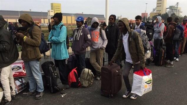 Des migrants font la file pour monter dans les autobus.