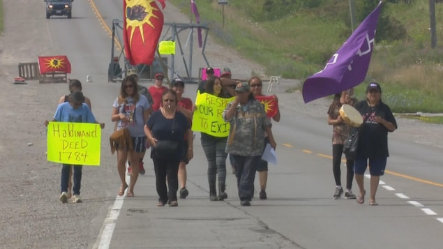 Des manifestants autochtones avancent sur une route.