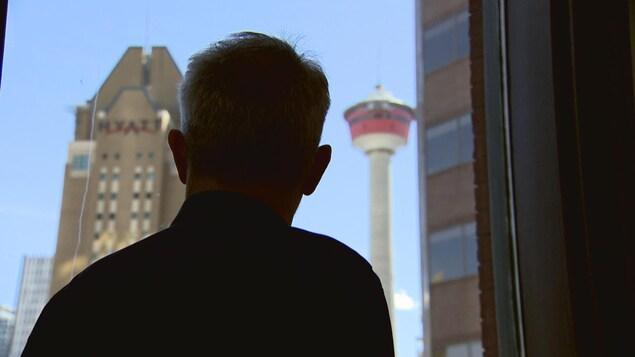 Un homme regarde par la fenêtre en direction de la tour de Calgary.