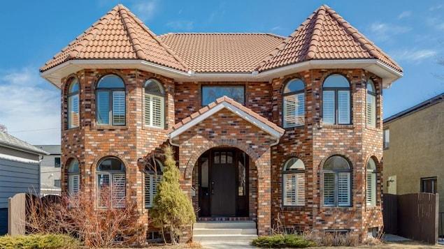 Maison en briques sur deux étages avec des tourelles de chaque côté de l'entrée.