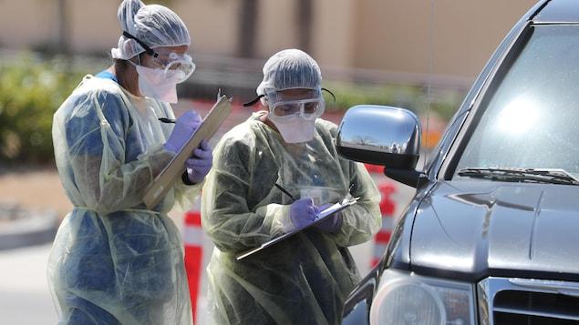Deux personnes en habit de protection prennent des notes près d'une voiture.