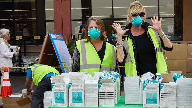 Des femmes présentes à un point de distribution de masques respiratoires en Californie.