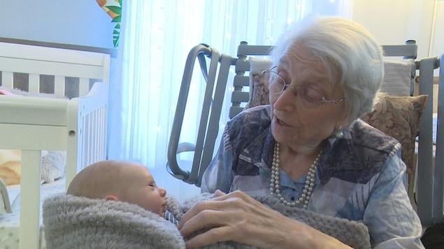 Une femme âgée tient une poupée de bébé.