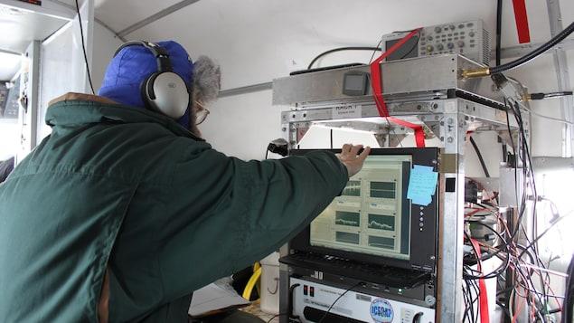 Un homme est de dos avec un gros manteau d'hiver et un bonnet bleu. Il travaille sur un ordinateur.