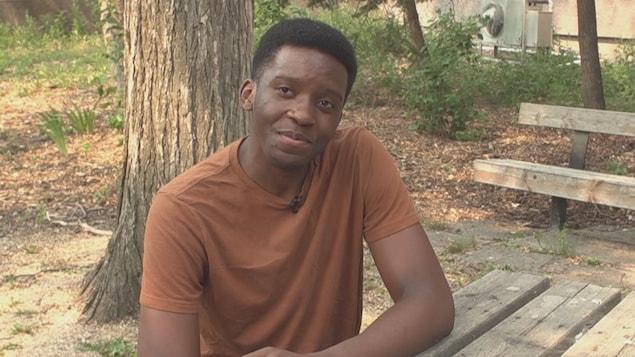 Calvin Lugalambi, en t-shirt, assis à l'extérieur.