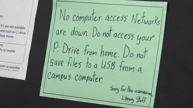 Une affiche dans la bibliothèque du collège avise les étudiants que le réseau internet est en panne et conseille de ne rien sauvegarder sur une clé USB à partir d'un ordinateur du campus.