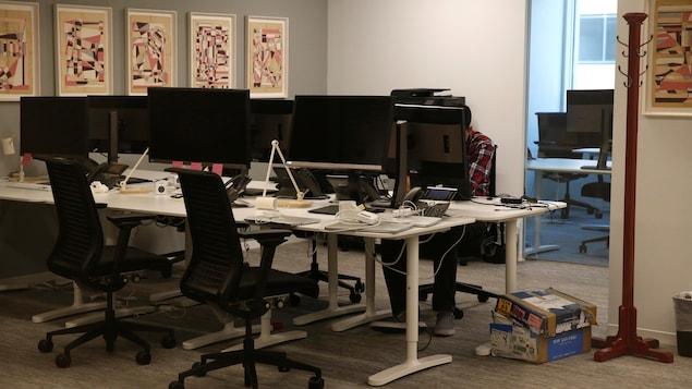 Aux murs, des oeuvres d'art cubistes sont affichées. Devant les écrans d'ordinateur, restent des chaises vides.