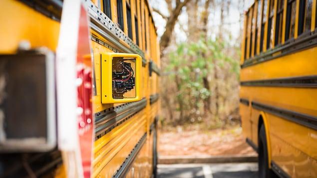 Une caméra installée sur un autobus avec un autre autobus à côté.